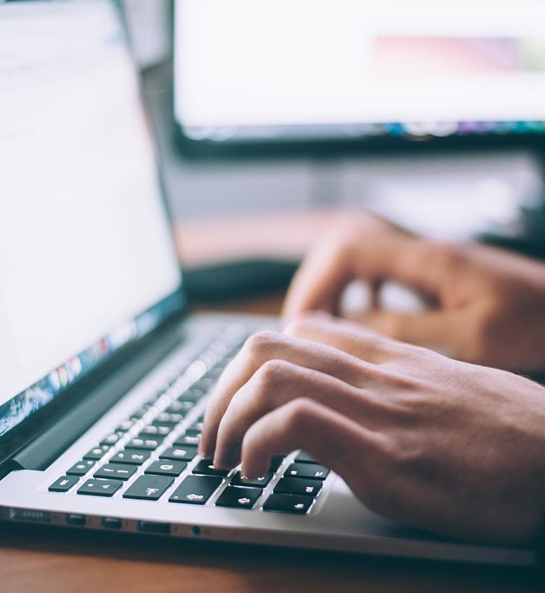 Mitarbeiter tippt auf Notebook-Tastatur